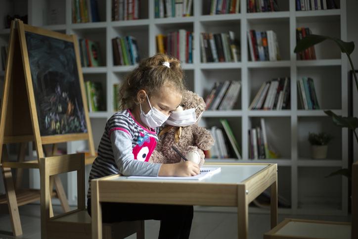 Little girl taking online courses in living room
