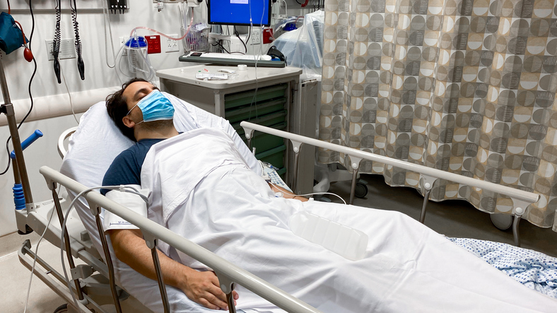 Latin man recovering in a hospital bed