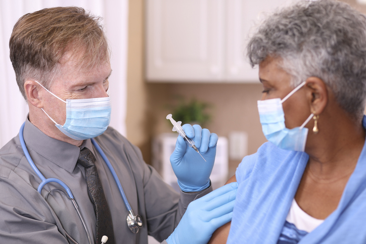 COVID-19: Doctor and senior adult, African descent patient, vaccine, masks.