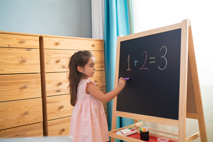 Little girl is studying math on the blackboard in her room