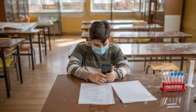 One school boy using phone in the classroom during Covid-19pandemics