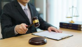 Judge gavel with Justice lawyers, counselor in suit or lawyer working on a documents at law firm in office.