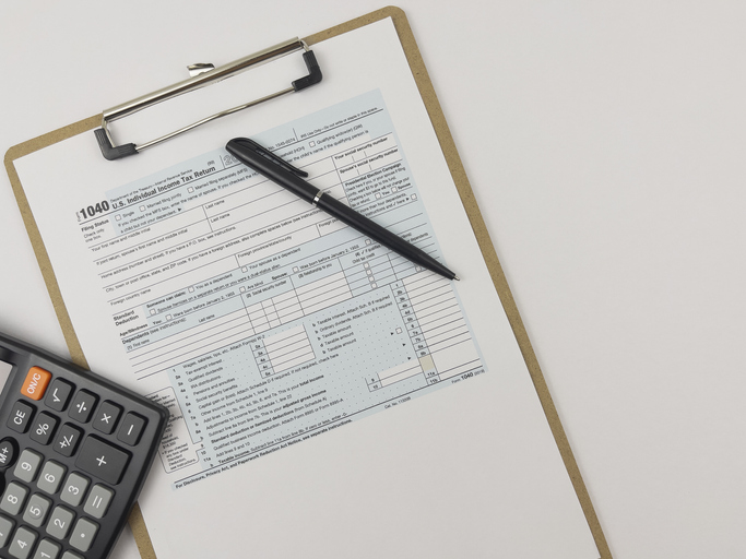 Printed Tax Form on Work Desk with Calculator and Pen.