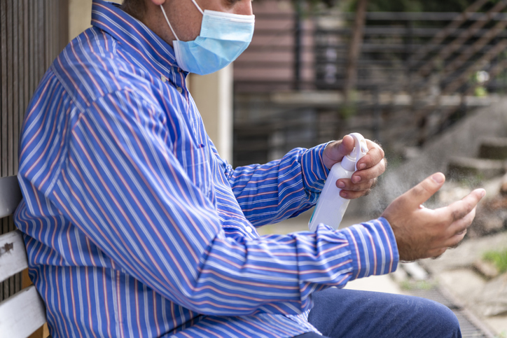Businessman with Surgical Face Mask is Sitting in the Backyard and Cleaning his Hands.