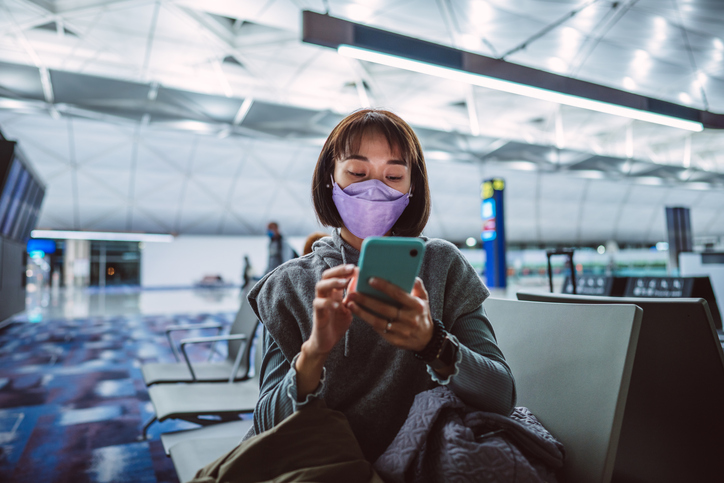Young Asian woman in protective face mask using smartphone joyfully while waiting for night flight in airport terminal