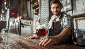 Bartender looking in camera serving beer