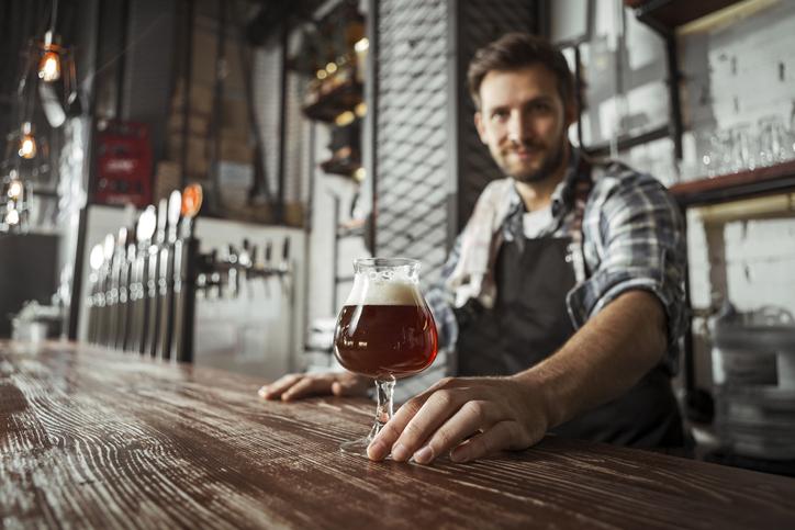 Bartender looking in camera serving beer