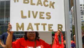 Black Lives Matter advocate holds a placard that says #...