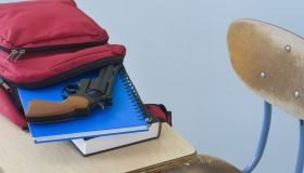 Backpack with book, notebook, and handgun on desk